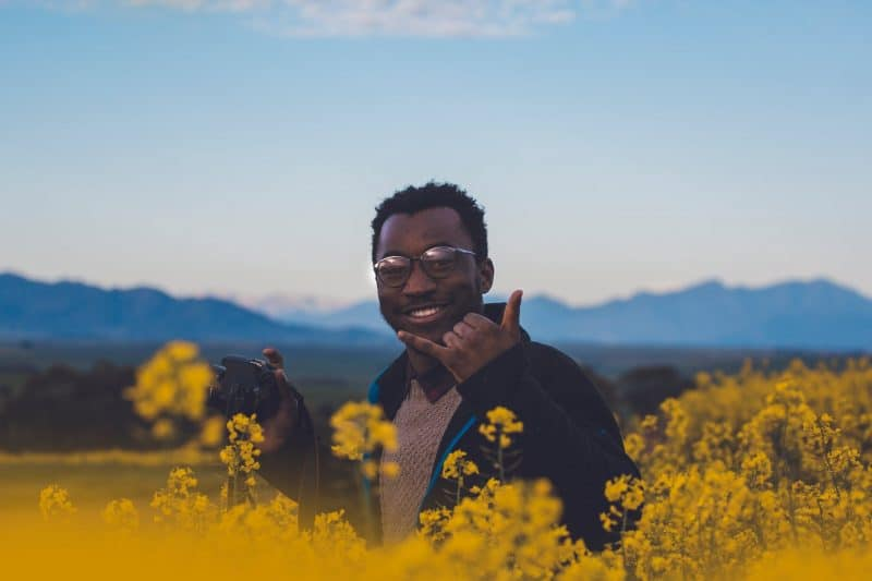 Man in Flowers With Camera