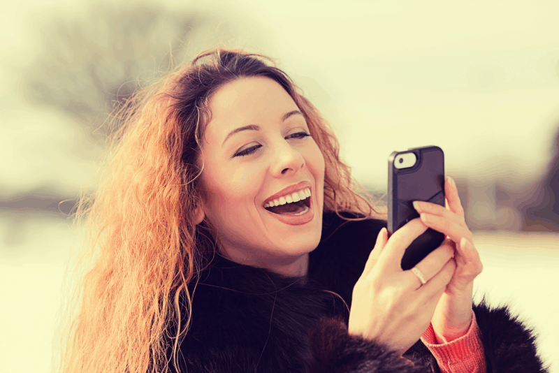 Woman Laughing at Phone